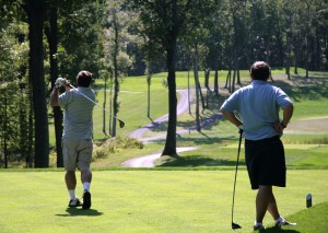 Two golfers teeing off for a round of golf on a nice course