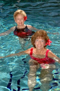 Two adult women swimming in a pool at a 55 and over community