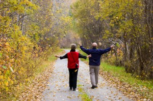Older couple taking a walk down a path on a beautiful autumn day