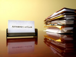 An elder care attorney's card and a stack of legal papers dealing with senior citizen issues