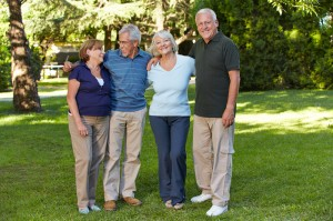 Four older people standing on the grass