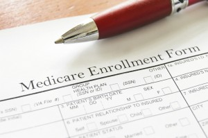 A pen laying next to a Medicare enrollment form