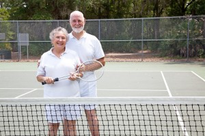 Older couple standing on a tennis court with racquets in hand