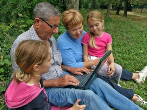Grandparents sitting with their grand daughters on a computer