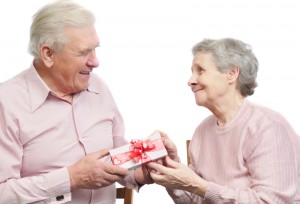 A senior citizen husband giving his elderly wife a small gift