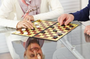 Residents of an independent living community playing a game of chess and checkers