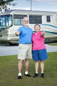 Couple standing in front of their new RV with thumbs up