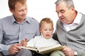 Dad and son reading a book together while sitting down