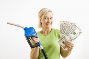 Woman holding a gas pump and a large hand of cash from savings on her fuel bill