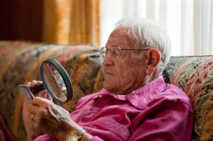 Man with an eye disease using a magnifying glass to see better