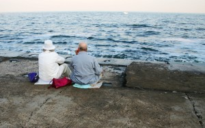Married couple sitting by the water having a long conversation about life