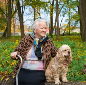 Elderly woman sitting on a park bench holding her cane and her pet dog