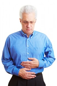 Man with IBD stands in pain holding his stomach