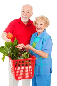 Married couple carrying a basket with fresh fruit and vegetables