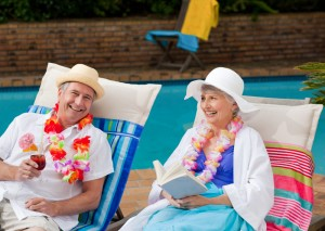 Older married people sitting by the pool in Florida enjoying both their cocktails and retirement