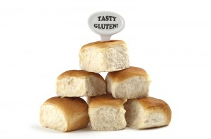 "Stack of bread rolls with sign that says ""Tasty Gluten"""