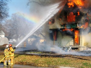 Firefighters putting out a home on fire with a large water hose