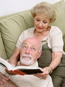 Bored man who's wife is reading to him while he lays on the couch